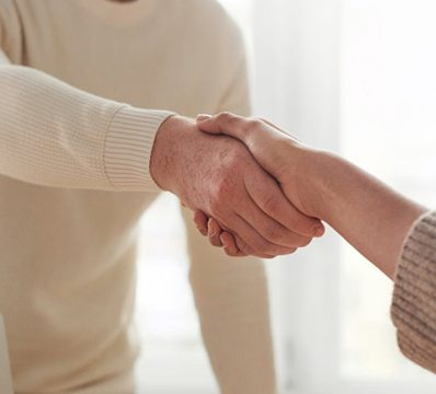 man in white cardigan shaking hands with woman out of frame